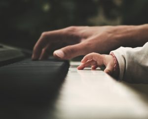 adult and child hand playing piano